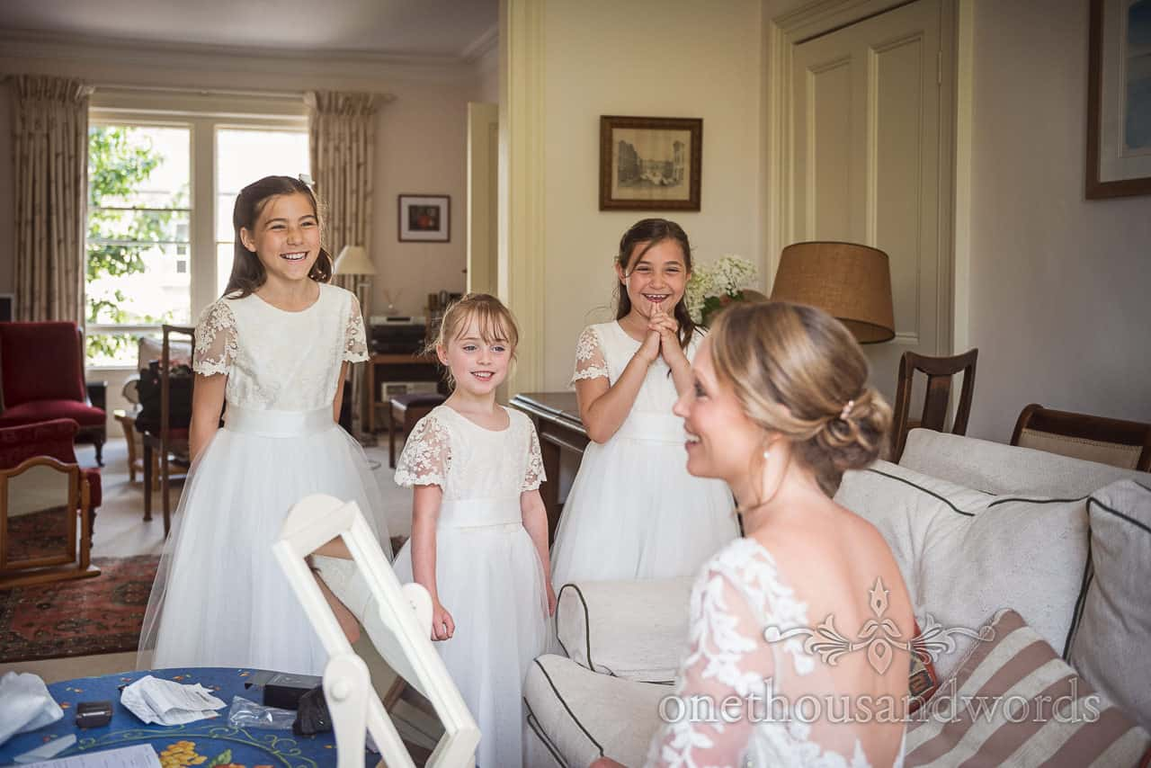 Flower girls in white dresses watch bride apply wedding makeup at family home on wedding morning documentary wedding photograph