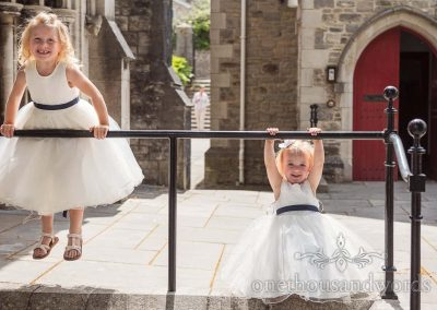 Happy flower girls in white dresses playing on railings outside Swanage church before wedding ceremony