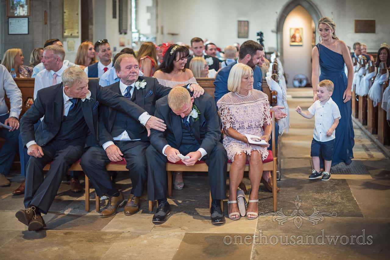 Groom is comforted by family members in church whilst waiting for bride in emotional wedding photograph