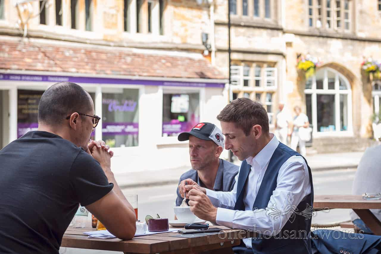 Groom sits with wedding guests on pub bench looking nervously at a coffee on wedding morning in Sherborne, Dorset