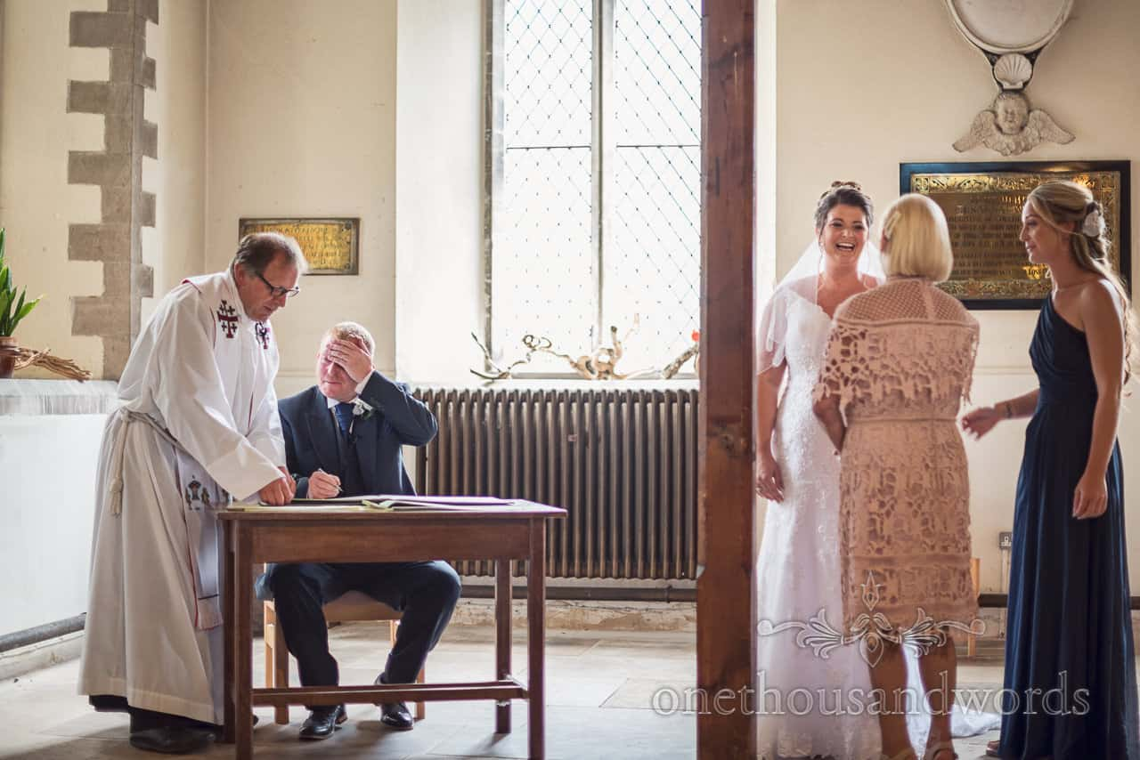 Documentary wedding photograph of groom rubbing head whilst signing register with bride laughing at family members