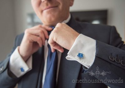 Groom adjusts his blue wedding tie as he shows off his Everton FC shirt cufflinks morning preparation photograph