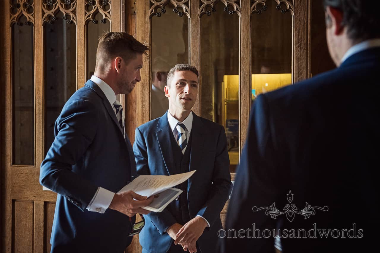 Groom waits for bride with groomsmen in blue wedding suits in doorway at Sherborne Abbey wedding photograph