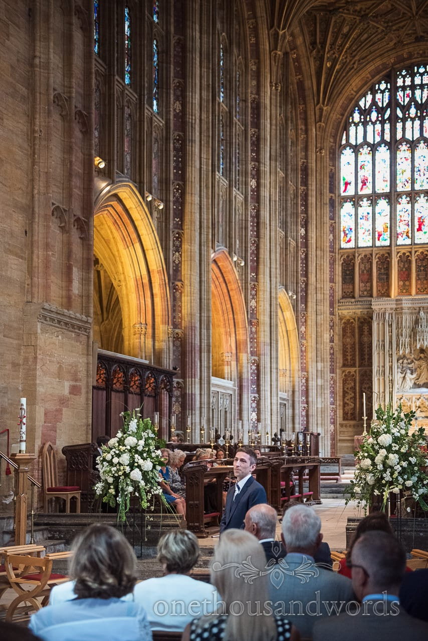 Groom waits for bride arrival with huge stone architecture of Sherborne Abbey wedding venue in Dorset