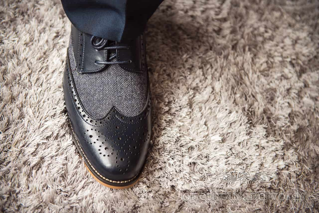 Groom's black and grey leather and fabric brogue wedding shoes on cream rug detail close up wedding photograph