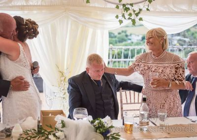 Emotional wedding photograph of groom's mother stroking his head as bride hugs her father after his wedding speech