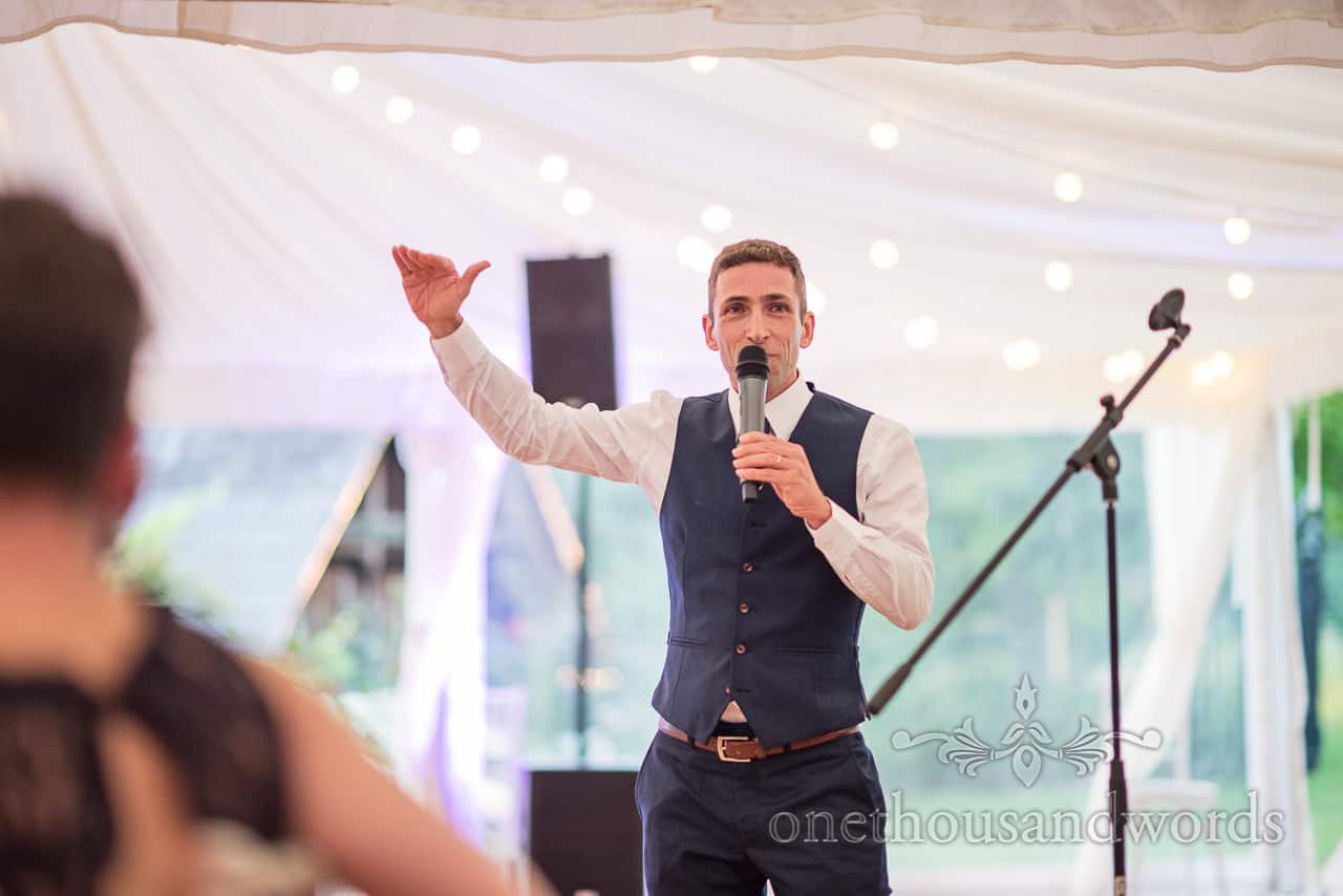 Grooms wears blue wedding waistcoat whilst making wedding speech about his height at Sherborne Castle wedding marquee