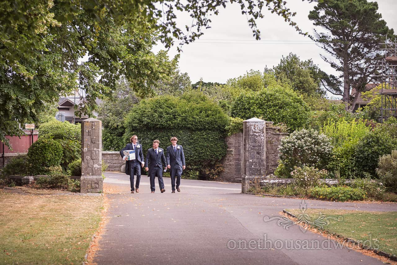 Documentary wedding photograph of groomsmen arriving at Swanage church driveway before wedding ceremony