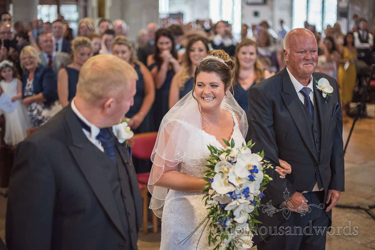 Happy smiling bride beams at husband as she arrives at top of aisle at Swanage church wedding ceremony