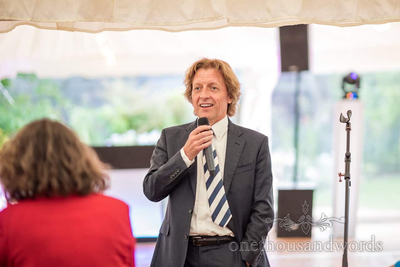 Relaxed master of ceremonies in grey suit with microphone at wedding breakfast announces arrival of bride and groom photograph