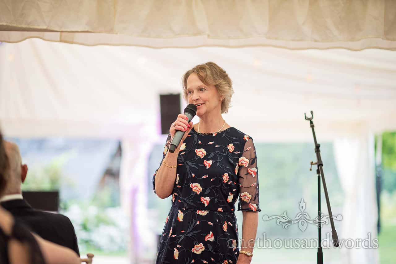 Mother of the bride in black flower pattern dress makes speech with microphone at Sherborne Castle wedding photograph