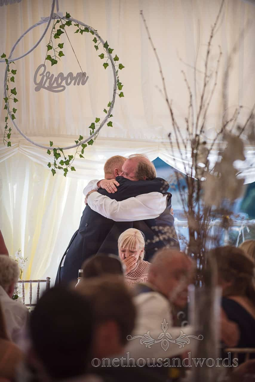 Emotional wedding photograph of mother of groom crying as groom hugs father behind top table in wedding marquee