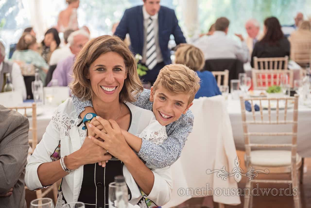 Hugging mother and son happily pose for a photograph whilst sat in Sherborne Castle wedding reception marquee