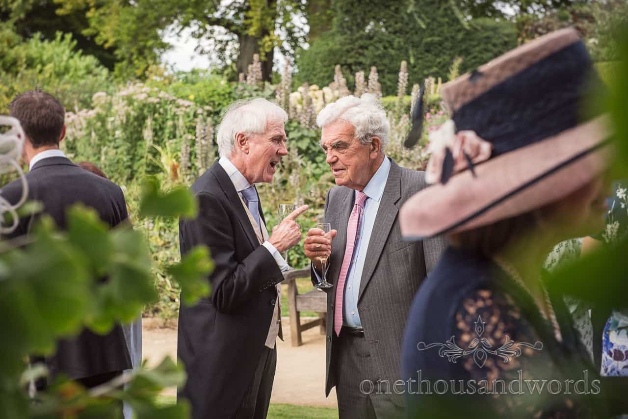 Older male wedding guests have animated conversation at Sherborne Castle wedding drinks reception in gardens