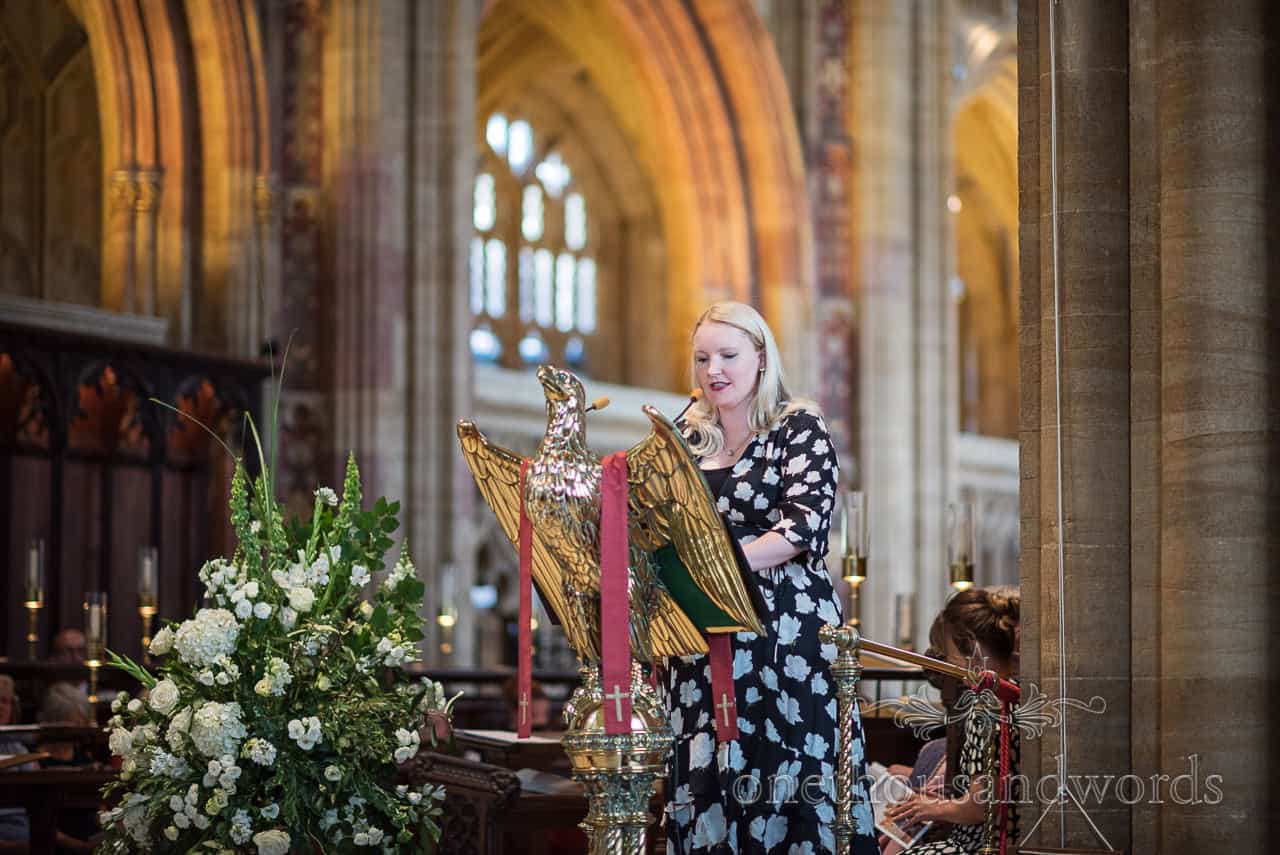 Female wedding guest in black and white dress makes reading from huge golden eagle at Sherborne Abbey wedding ceremony