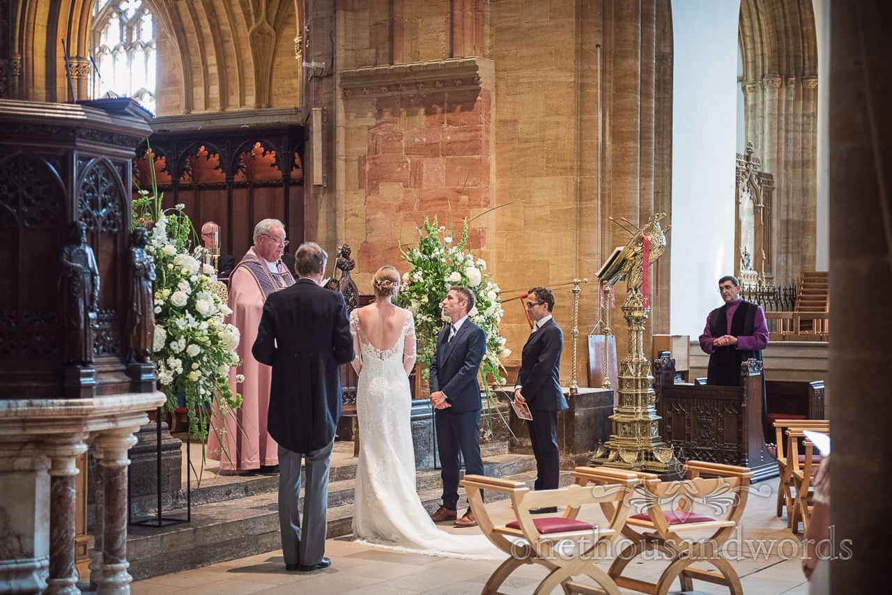 Sherborne Abbey wedding ceremony photograph of vicar, wedding couple, father of bride and best man at top of aisle