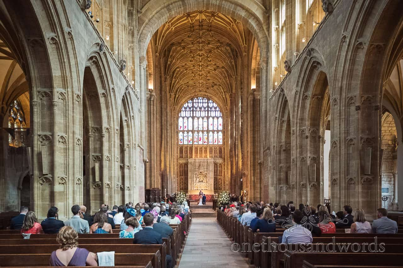Bride and groom kneel at altar at Sherborne Abbey wedding ceremony during wedding prayers and blessings wide angle photograph