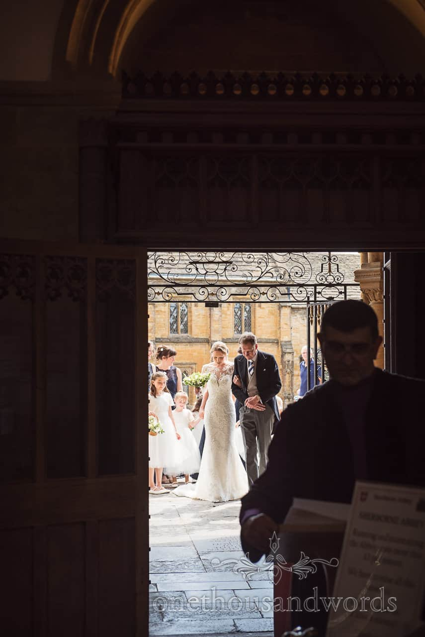Father of bride arrives in doorway with his daughter at Sherborne Abbey wedding venue in Dorset