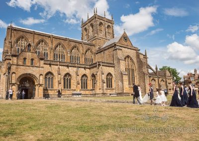 Bridal party arrives at Sherborne Abbey wedding venue in Dorset on summers day with blue skies photograph