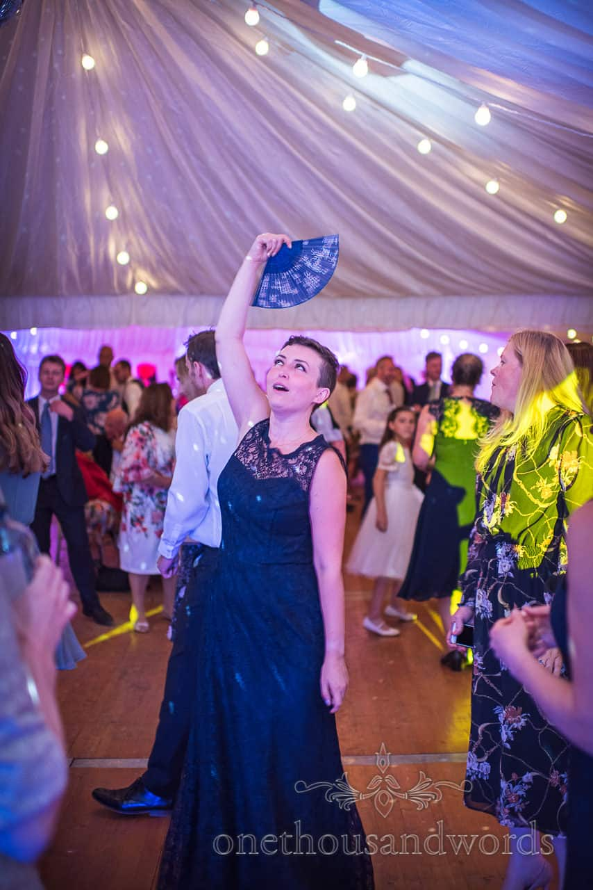 Sherborne Castle wedding evening photograph of bridesmaid dancing with blue fan on dance floor