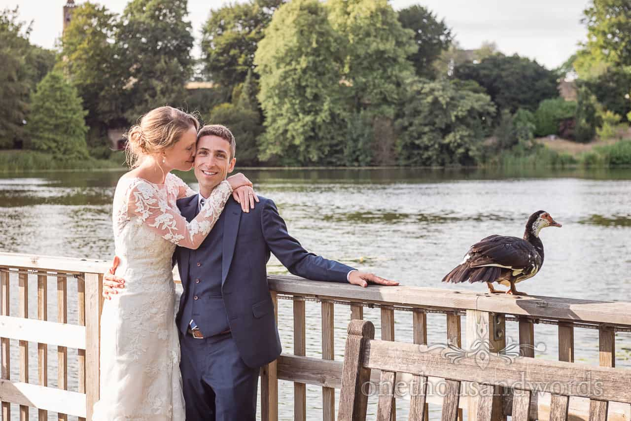 Sherborne Castle wedding photographs of bride and groom cuddling on wooden jetty at lake with Duck