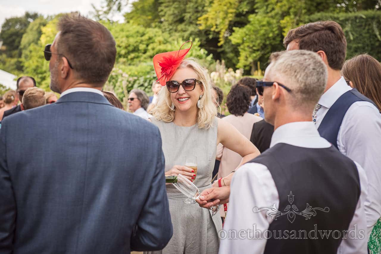 Sherborne Castle wedding venue female guests in red fascinator at drinks reception documentary wedding photograph