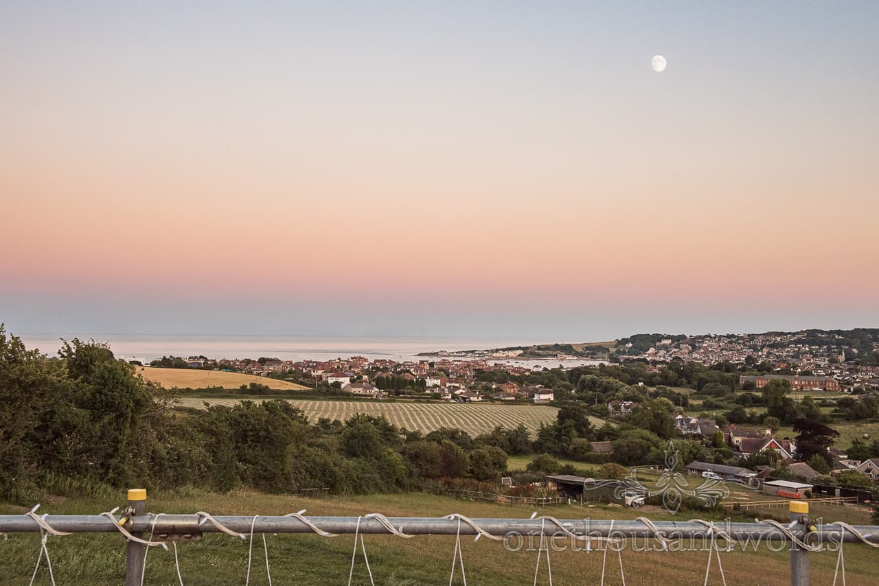 Sunset over Swanage and sea with moon view on evening from Purbeck marquee wedding photographs