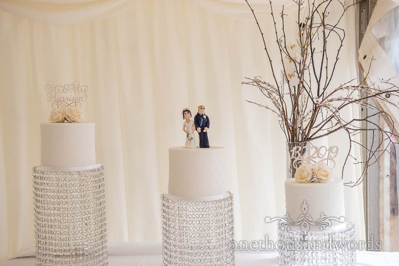 Three simple white wedding cakes with personalised cake toppers and cherry blossoms stick decorations