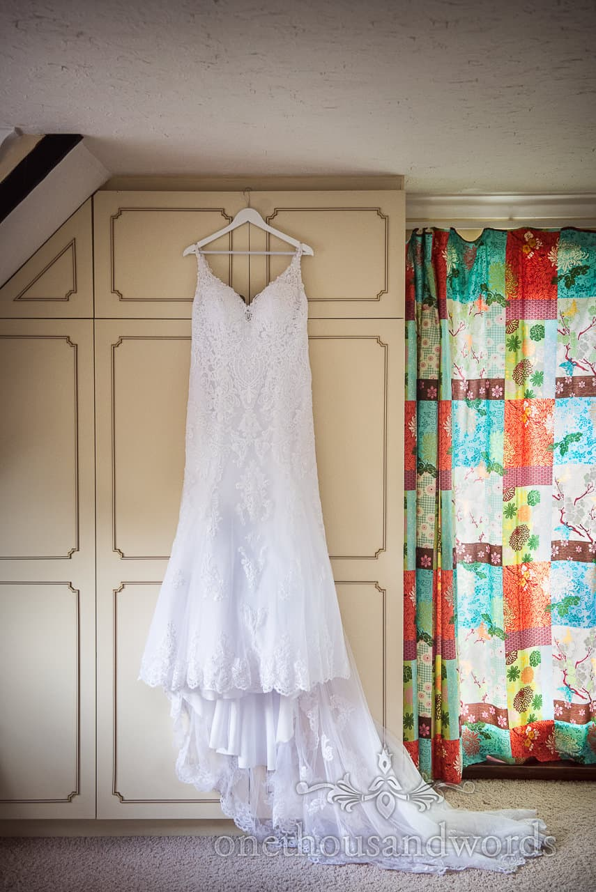 Detailed white a line backless wedding dress hangs on wardrobe door with patchwork pattern multi coloured curtains