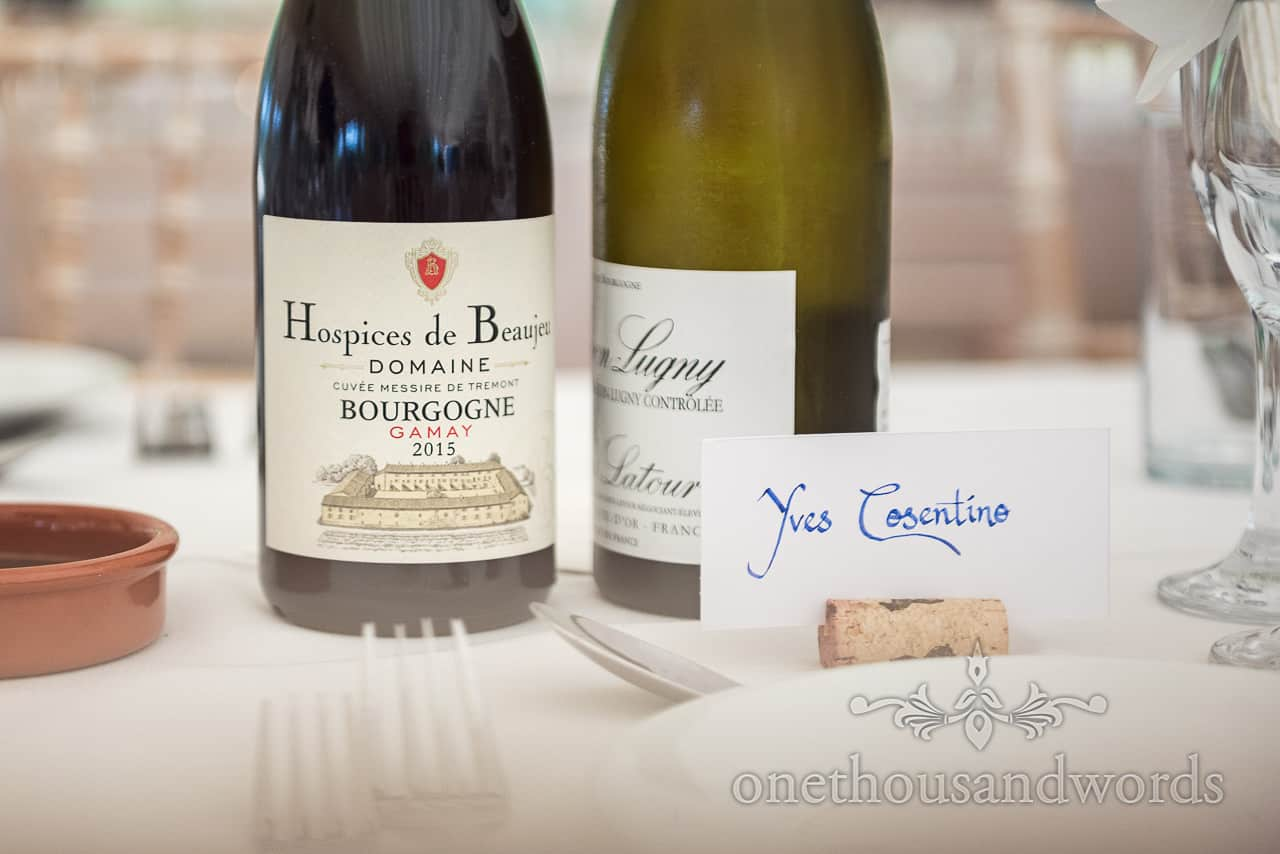French red and white wine bottles on wedding tables with hand written wedding name place sign in wine cork