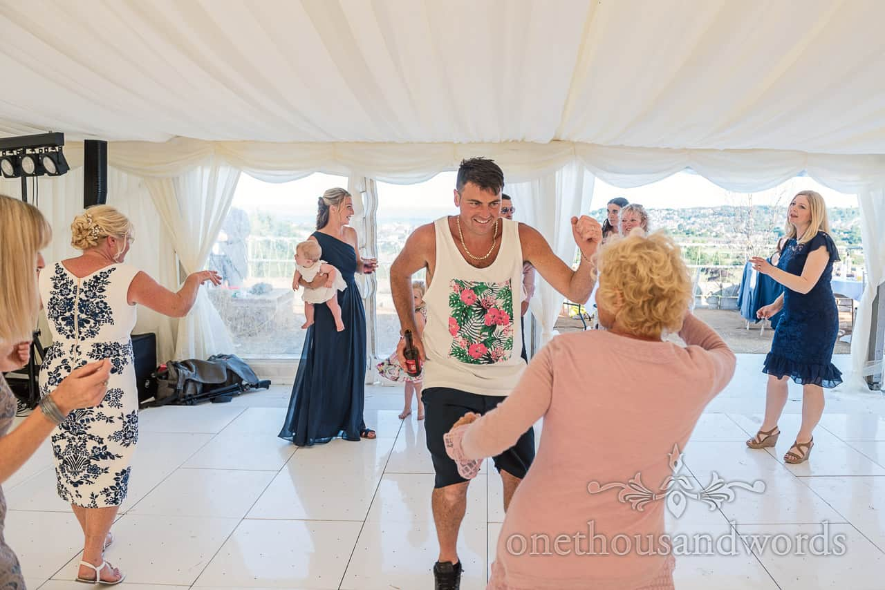 Wedding guest in casual summer clothing animated dancing on reflective white dance floor in wedding marquee