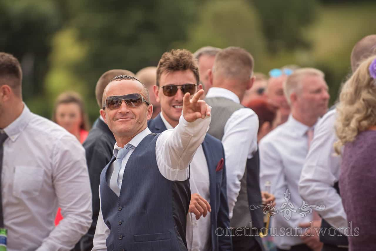 Wedding guest in group makes peace sign to camera wearing sunglasses and grey waistcoat