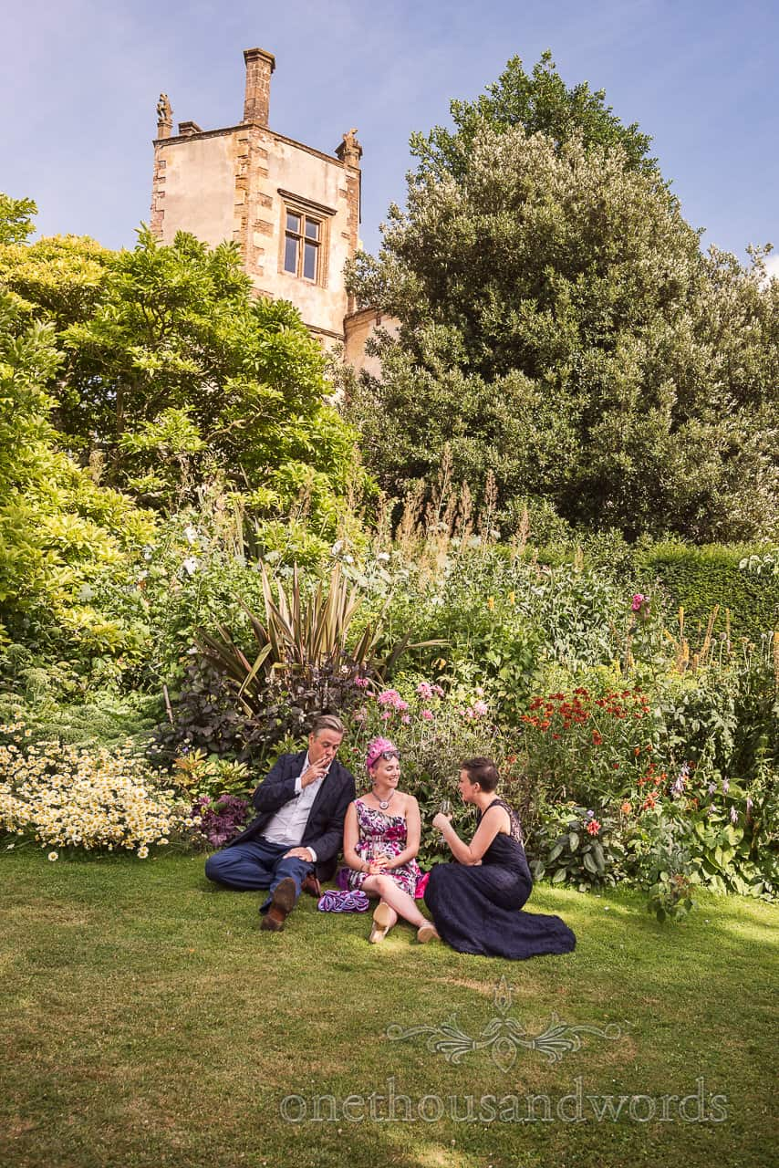 Wedding guests chat in the shade on the lawns and gardens at drinks reception at Sherborne Castle