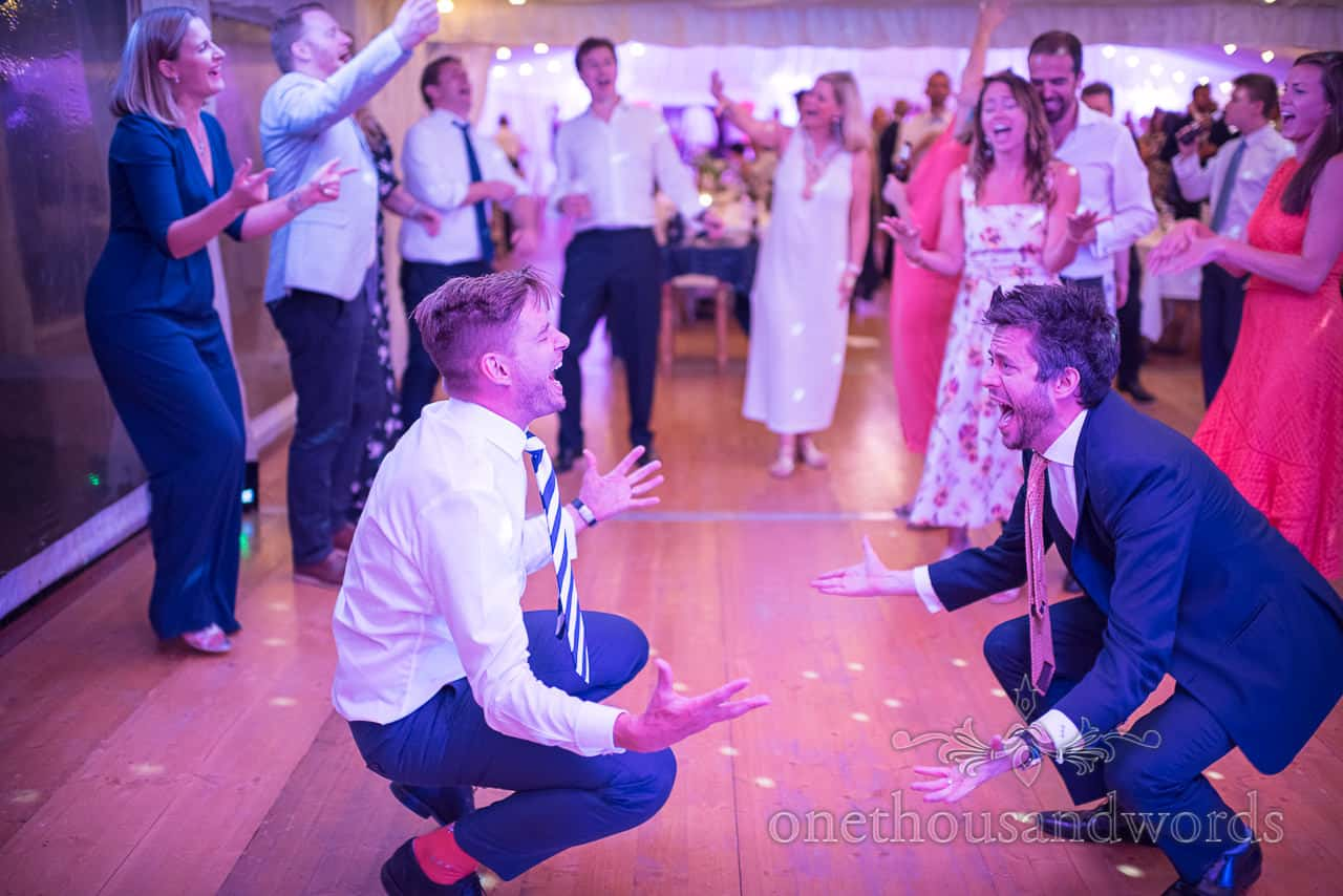 Wedding guests crazy dancing and singing on dance floor in Sherborne Castle wedding marquee