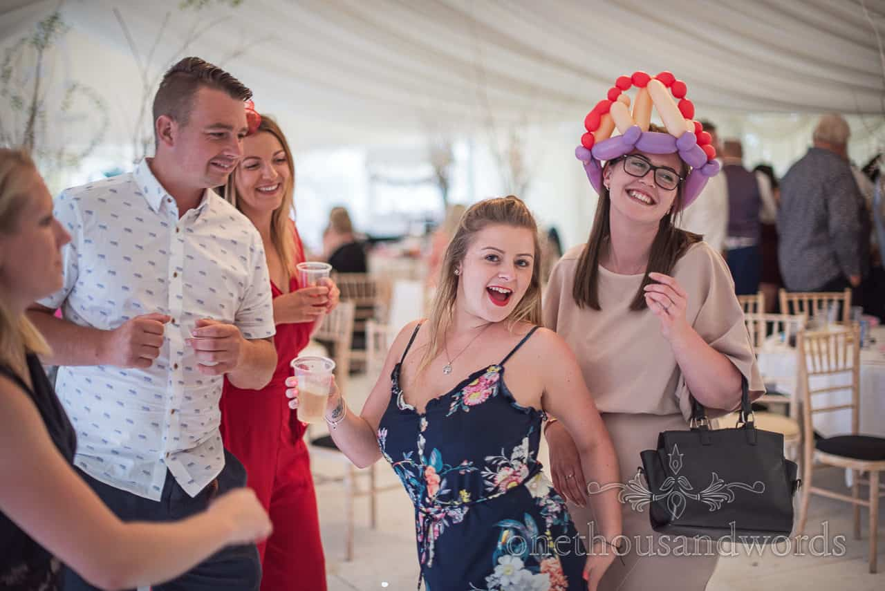 Wedding guests dancing with balloon hat and drinks in hand at marquee evening reception
