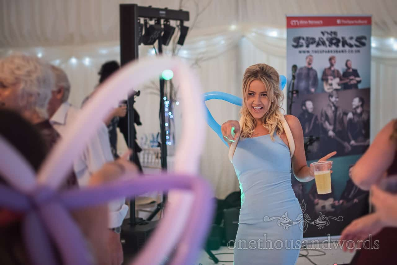 Wedding guest in sky blue dress dancing in marquee wearing balloon angel wings with drink in hand and pointing