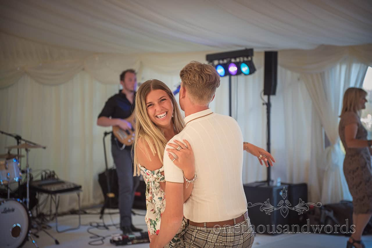 Smiling wedding guests dancing together in wedding marquee to Dorset wedding band with disco lights