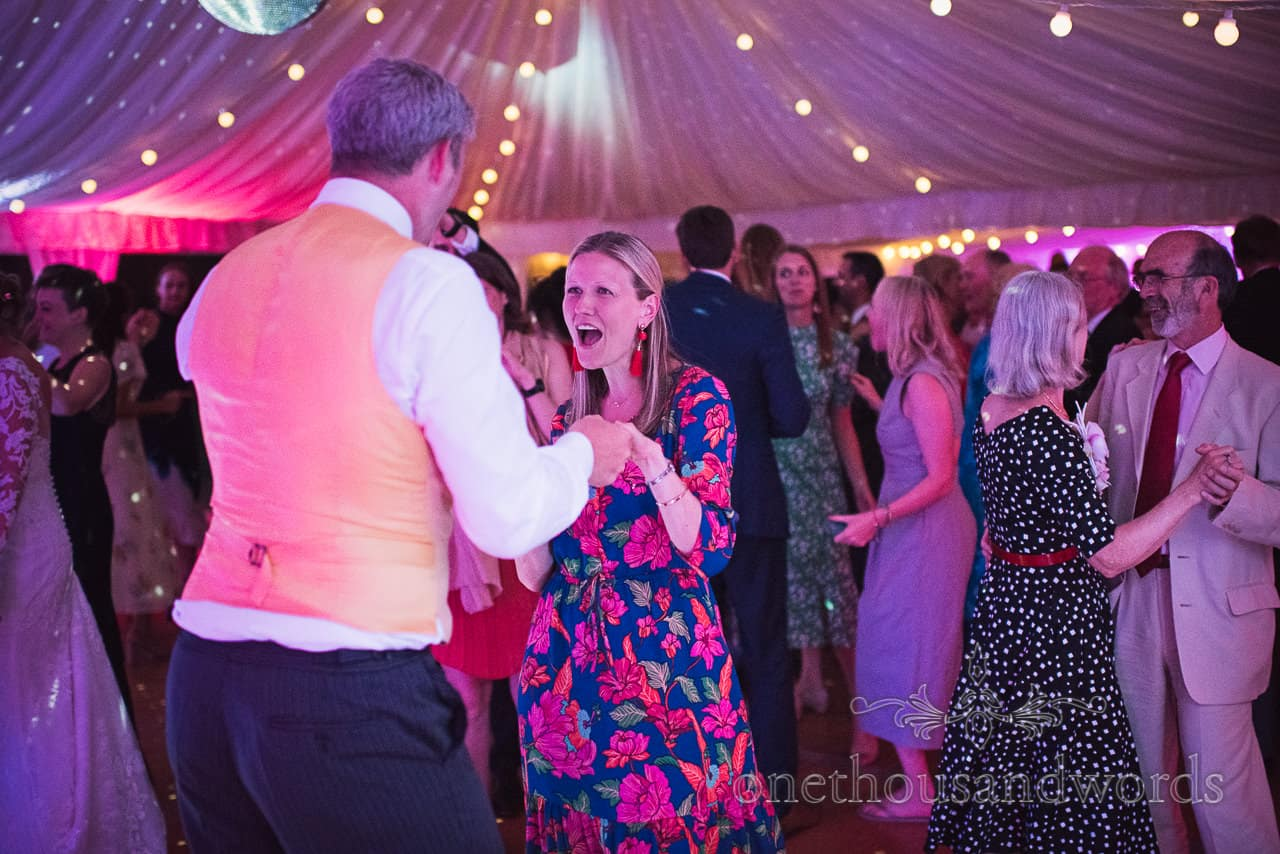 Wedding guests singing and dancing under disco lighting at Sherborne Castle wedding marquee in Dorset