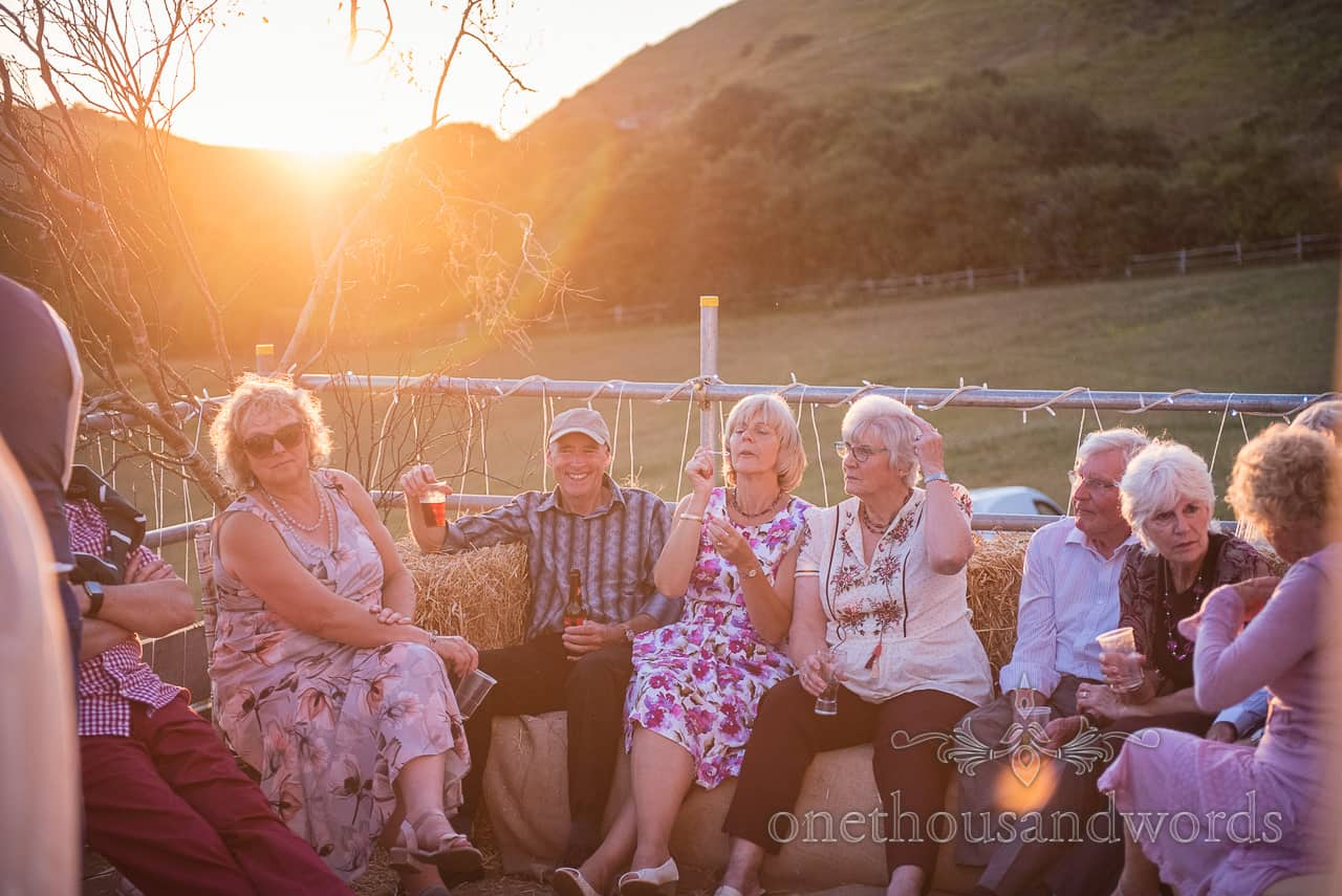 Wedding guests enjoying countryside sunset drinks sitting on straw bales on scaffold terrace in Purbeck countryside