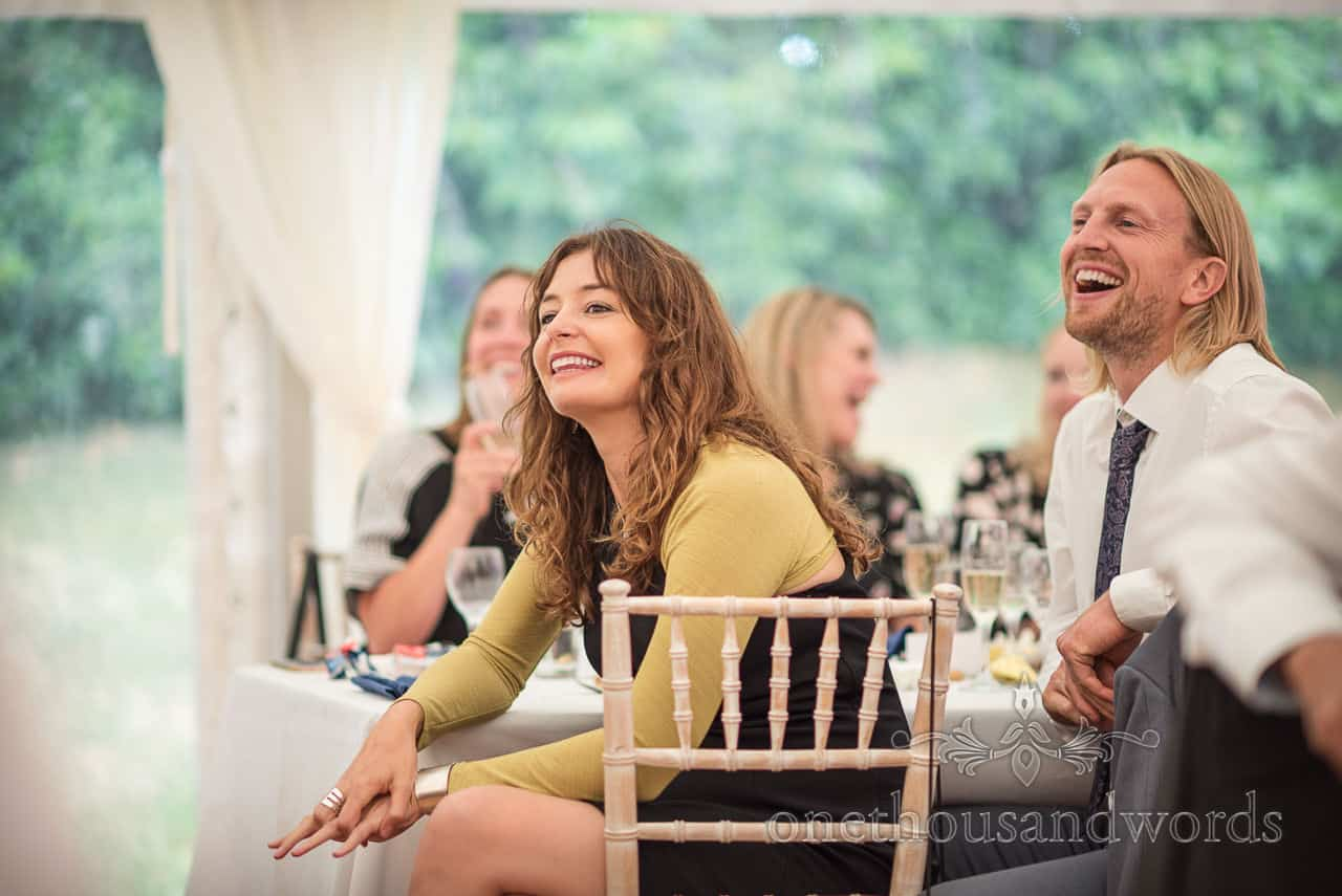 Happy wedding guests laughing in marquee during wedding breakfast at Sherborne Castle photographs by one thousand words