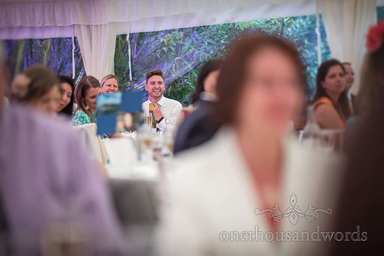 Documentary wedding photograph of wedding guests laughing in marquee at wedding evening speeches