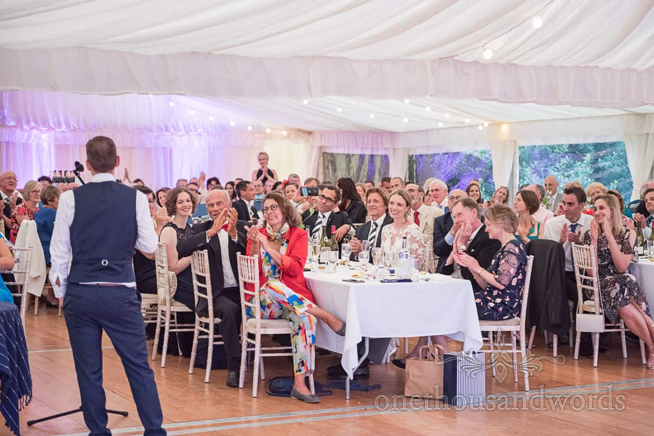 Wedding guests listen to speeches and clap in Sherborne Castle wedding marquee in Dorset by one thousand words