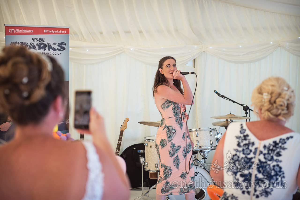 Wedding guest wearing pink feather pattern dress sings in microphone to bride and guests in wedding marquee