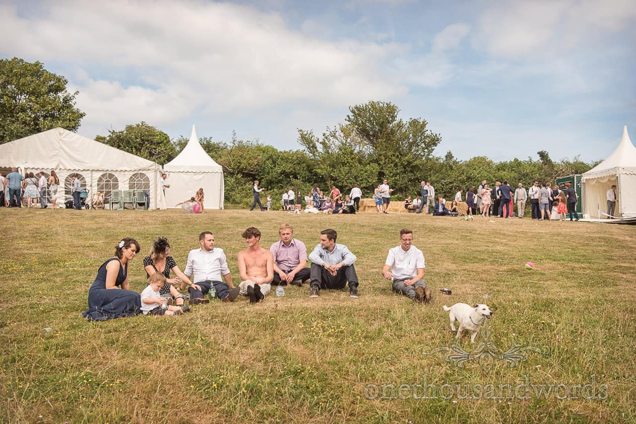 Wedding guests sat relaxing in countryside field in the summer sun as a ball is thrown for the family dog