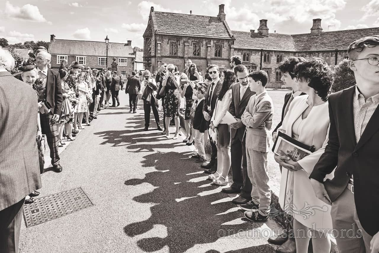 Wedding guests animated shadows line up outside Sherborne Abbey wedding venue in summer sunshine