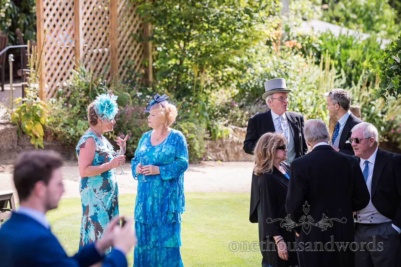 Wedding guests in blue dresses and tail coats at Sherborne Castle wedding drinks reception in gardens