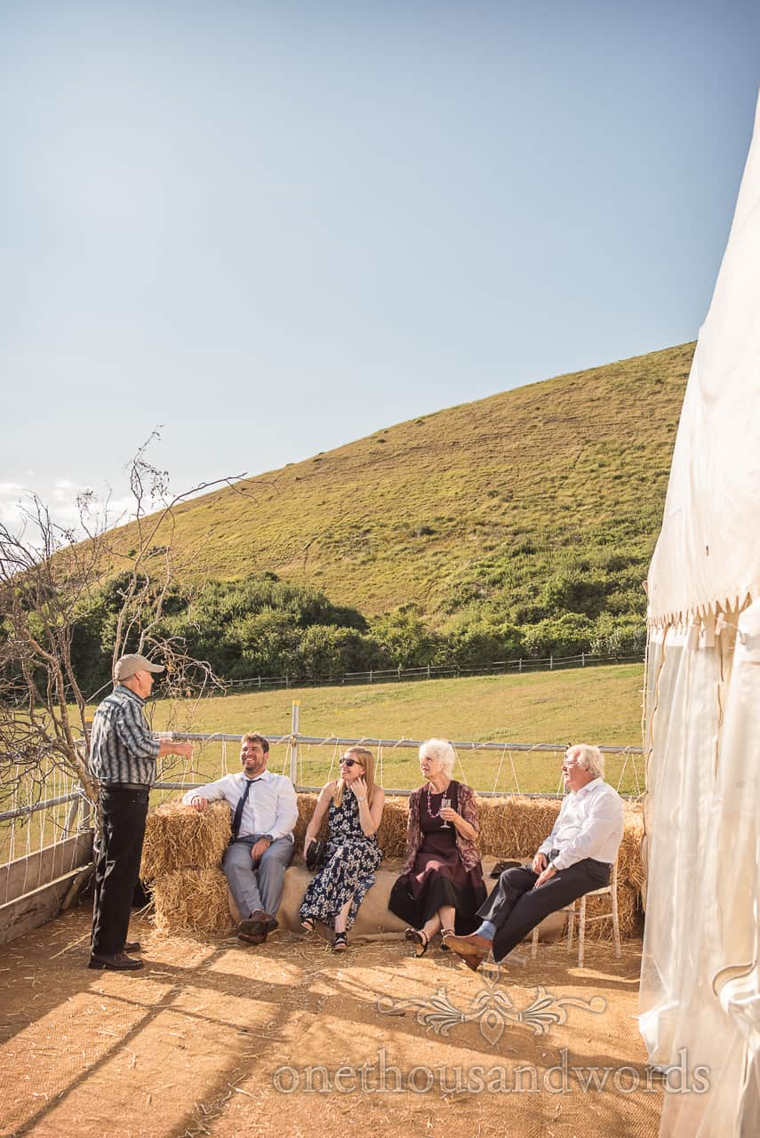 Wedding guests sit on straw bales at wedding drinks reception on countryside marquee sun terrace in Swanage, Dorset