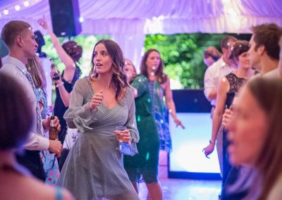 Wedding guests strutting on the dance floor under glitter ball at Sherborne Castle wedding marquee by one thousand words