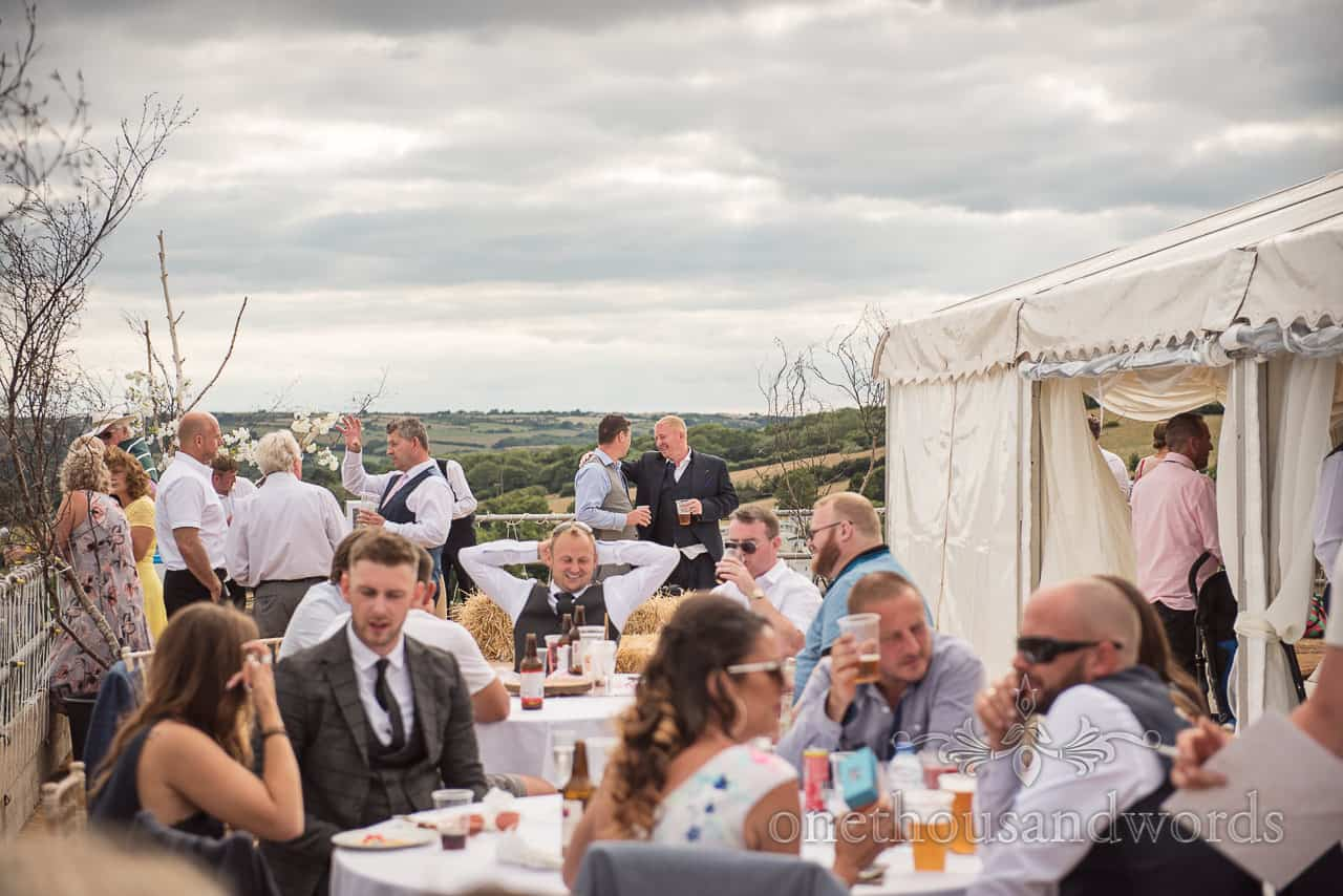 Wedding guests enjoy countryside views on wedding marquee sun terrace with groom in happy conversation