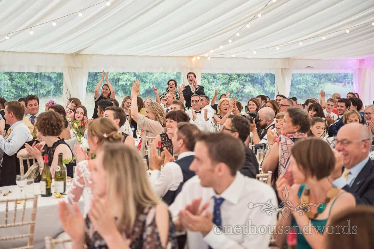 Wedding guests all toast speeches in Sherborne Castle wedding marquee at Dorset wedding by one thousand words wedding photography